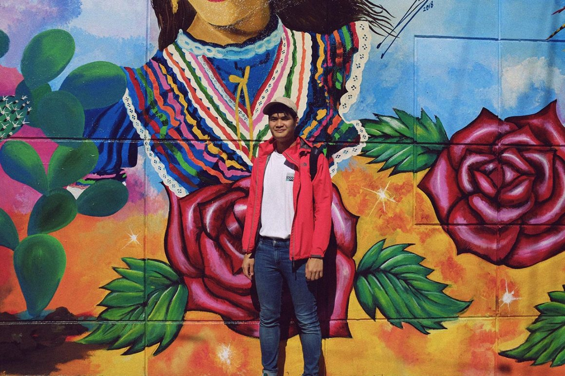 Boy in front of mural in the Mission in San Francisco