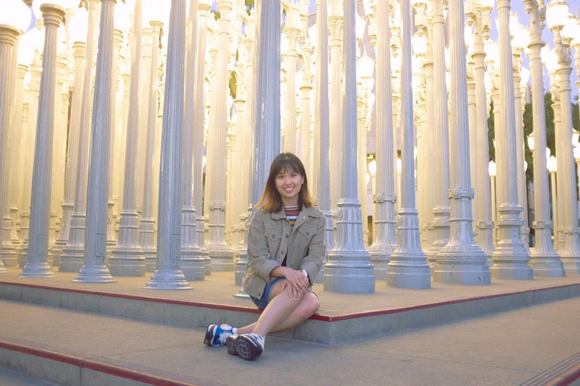 Girl sitting in front of Urban Lights attraction at LACMA